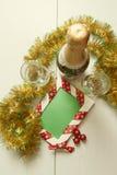 Πρότυπο ευχετήριων καρτών φιαγμένο από δύο γυαλιά και μπουκάλι της σαμπάνιας με τις σφαίρες που κρεμούν στην κορδέλλα, tinsel και Στοκ Φωτογραφία