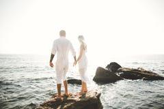 Πρότυπο ζεύγος μόδας με τη δερματοστιξία που θέτει την εξωτερική θάλασσα nea Στοκ Φωτογραφία