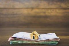 Πρότυπο και χρήματα σπιτιών στο ξύλινο υπόβαθρο Στοκ εικόνα με δικαίωμα ελεύθερης χρήσης