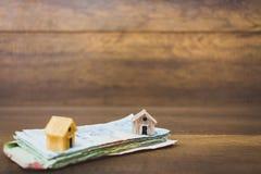 Πρότυπο και χρήματα σπιτιών στο ξύλινο υπόβαθρο Στοκ Εικόνα