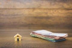 Πρότυπο και χρήματα σπιτιών στο ξύλινο υπόβαθρο Στοκ φωτογραφία με δικαίωμα ελεύθερης χρήσης