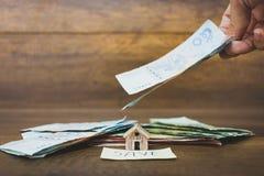 Πρότυπο και χρήματα σπιτιών στο ξύλινο υπόβαθρο Στοκ Φωτογραφία