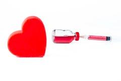 Πρότυπο καρδιών με μια φιάλη γυαλιού που γεμίζουν με ένα κόκκινο χημικό ρευστό Στοκ Φωτογραφία