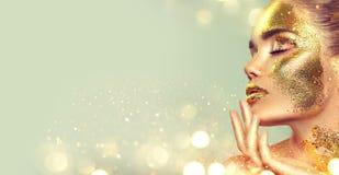 Πρότυπο κορίτσι μόδας ομορφιάς με το χρυσό δέρμα makeup και σώμα, χρυσό υπόβαθρο κοσμημάτων Χρυσή τέχνη σωμάτων Τέχνη μόδας στοκ εικόνες