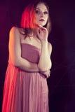 Πρότυπο κορίτσι μόδας που φορά τα μοντέρνα ενδύματα, ανοικτό ροζ τοποθέτηση παλτών στο γκρίζο υπόβαθρο στο στούντιο προκλητική γυ Στοκ φωτογραφίες με δικαίωμα ελεύθερης χρήσης