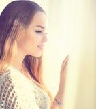 Πρότυπο κορίτσι ομορφιάς που φαίνεται έξω το παράθυρο Στοκ Εικόνα