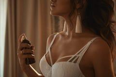 Πρότυπο κορίτσι όμορφου και σαγηνευτικού brunette με το τέλειο προκλητικό σώμα μοντέρνο lingerie δαντελλών που εφαρμόζει το άρωμα στοκ εικόνες με δικαίωμα ελεύθερης χρήσης