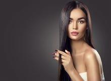 Πρότυπο κορίτσι brunette ομορφιάς σχετικά με μακρυμάλλη στοκ εικόνες