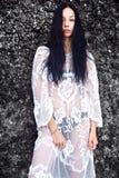 Πρότυπο με σκοτεινό μακρυμάλλη στη διαφανή άσπρη μακροχρόνια τοποθέτηση φορεμάτων μπλουζών κοντά στους βράχους Στοκ εικόνες με δικαίωμα ελεύθερης χρήσης