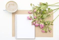 Πρότυπο με τα κενά ρόδινα τριαντάφυλλα σημειωματάριων, φλιτζανιών του καφέ και λίγων κήπων πρωί ζωής ακόμα Στοκ Εικόνα