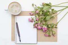 Πρότυπο με τα κενά ρόδινα τριαντάφυλλα σημειωματάριων, φλιτζανιών του καφέ και λίγων κήπων πρωί ζωής ακόμα Στοκ Φωτογραφίες