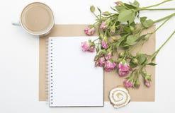 Πρότυπο με τα κενά ρόδινα τριαντάφυλλα σημειωματάριων, φλιτζανιών του καφέ και λίγων κήπων πρωί ζωής ακόμα Στοκ φωτογραφίες με δικαίωμα ελεύθερης χρήσης