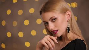 Πρότυπο μόδας με την όμορφη ξανθή τοποθέτηση τρίχας στα κίτρινα φω'τα bokeh, σε αργή κίνηση απόθεμα βίντεο