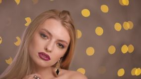 Πρότυπο μόδας με την όμορφη τοποθέτηση τρίχας στα κίτρινα φω'τα bokeh, σε αργή κίνηση απόθεμα βίντεο