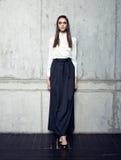 Πρότυπο μόδας που φορά το άσπρο πουκάμισο και πολύ τη μαύρη τοποθέτηση φουστών στο στούντιο Στοκ Εικόνες