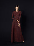 Πρότυπο μόδας που φορά το μακρύ καφέ φόρεμα στο μαύρο υπόβαθρο Στοκ Εικόνες