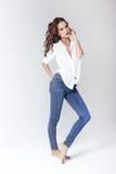 Πρότυπο μόδας σε μια μπλούζα και τα τζιν χωρίς παπούτσια Στοκ Φωτογραφία