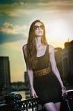 Πρότυπο μόδας στην οδό με τα γυαλιά ηλίου και το απότομα μαύρο φόρεμα Στοκ Εικόνες