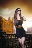 Πρότυπο μόδας στην οδό με τα γυαλιά ηλίου και το απότομα μαύρο φόρεμα Στοκ Εικόνα