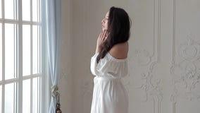 Πρότυπο μόδας Brunette στην άσπρη τοποθέτηση φορεμάτων στη κάμερα στο στούντιο απόθεμα βίντεο