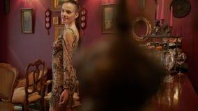 Πρότυπο νέων κοριτσιών που χαμογελά και που θέτει σε ένα κομψό λαμπιρίζοντας φόρεμα κομμάτων αναδρομικό ύφος, βιομηχανία μόδας, ο φιλμ μικρού μήκους