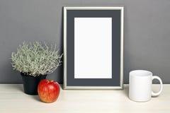 Πρότυπο πλαισίων με το δοχείο, την κούπα και το μήλο εγκαταστάσεων στο ξύλινο ράφι Στοκ φωτογραφία με δικαίωμα ελεύθερης χρήσης
