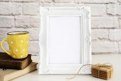 Πρότυπο πλαισίων Άσπρη χλεύη πλαισίων επάνω Κίτρινο φλιτζάνι του καφέ με τα άσπρα σημεία, Cappuccino, Latte, παλαιά βιβλία, μπισκ στοκ εικόνες