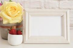 Πρότυπο πλαισίων Άσπρη χλεύη πλαισίων επάνω Πλαίσιο εικόνων κρέμας, βάζο με τα ρόδινα τριαντάφυλλα, φράουλες στο χρυσό κύπελλο Πρ Στοκ φωτογραφίες με δικαίωμα ελεύθερης χρήσης