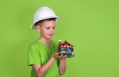 Πρότυπο σπιτιών στα χέρια παιδιών Έννοια οικογενειακών σπιτιών - πορτρέτο του γ Στοκ Φωτογραφία
