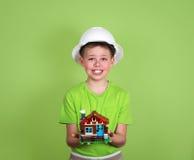 Πρότυπο σπιτιών στα χέρια child's Έννοια οικογενειακών σπιτιών - πορτρέτο Στοκ Φωτογραφία