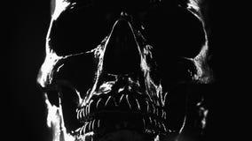 Πρότυπο του ανθρώπινου κρανίου που χρωματίζεται με το Μαύρο στο σκοτεινό υπόβαθρο με το μεταβλητό φωτισμό Έννοια του φόβου και τη απόθεμα βίντεο