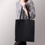 Πρότυπο Το κορίτσι κρατά τη μαύρη τσάντα βαμβακιού tote Στοκ Εικόνες