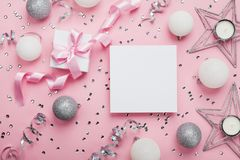 Πρότυπο Χριστουγέννων με το κενό κενό εγγράφου, το κιβώτιο δώρων και τη διακόσμηση στη ρόδινη τοπ άποψη υποβάθρου Επίπεδος βάλτε Στοκ Εικόνα