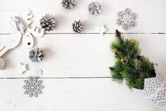 Πρότυπο Χριστουγέννων σε ένα άσπρο ξύλινο υπόβαθρο με snowflakes, ένα ελάφι και ένα χριστουγεννιάτικο δέντρο Επίπεδος βάλτε, τοπ  Στοκ Εικόνες