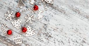 Πρότυπο Χριστουγέννων Υπόβαθρο με τα ξύλινα παιχνίδια και το κόκκινο Χριστουγέννων Στοκ Εικόνες