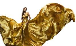 Πρότυπο χρυσό φόρεμα μυγών μόδας, κομψή κυματίζοντας εσθήτα γυναικών στοκ εικόνα με δικαίωμα ελεύθερης χρήσης