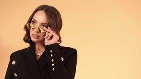 Πρότυπο Brunette στα μοντέρνα αντανακλημένα γυαλιά ηλίου και το μαύρο σακ απόθεμα βίντεο