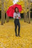 Πρότυπο Brunette στο φύλλωμα πτώσης με την ομπρέλα και το ποτό Στοκ εικόνα με δικαίωμα ελεύθερης χρήσης