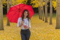 Πρότυπο Brunette στο φύλλωμα πτώσης με την ομπρέλα και το ποτό Στοκ Εικόνες