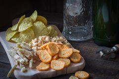 Πρόχειρα φαγητά για την μπύρα και την κούπα μπύρας, σε έναν ξύλινο πίνακα, σε έναν φραγμό Φυστίκια, κομμάτια των ψαριών, κροτίδες Στοκ φωτογραφία με δικαίωμα ελεύθερης χρήσης