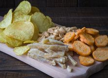Πρόχειρα φαγητά για την μπύρα στον πίνακα στο μπαρ Φυστίκια, κομμάτια των ψαριών, κροτίδες, τσιπ Κινηματογράφηση σε πρώτο πλάνο Στοκ εικόνες με δικαίωμα ελεύθερης χρήσης