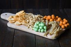 Πρόχειρα φαγητά για την μπύρα στον πίνακα στο μπαρ Φυστίκια, φυστίκια σε ένα κοχύλι, κομμάτια των ψαριών, κροτίδες Στοκ Εικόνα