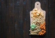 Πρόχειρα φαγητά για την μπύρα στον πίνακα στο μπαρ Φυστίκια, φυστίκια σε ένα κοχύλι, κομμάτια των ψαριών, κροτίδα Τοπ όψη Copyspa Στοκ φωτογραφία με δικαίωμα ελεύθερης χρήσης