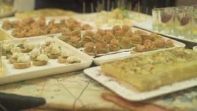 Πρόχειρα φαγητά και καναπεδάκια στον πίνακα μπουφέδων στο γεγονός Ορεκτικά πρόχειρα φαγητά στον πίνακα κομμάτων στο βράδυ διακοπώ απόθεμα βίντεο