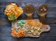 Πρόχειρα φαγητά σε μπύρα και δύο κούπες της ελαφριάς μπύρας, σε έναν ξύλινο πίνακα, σε έναν φραγμό Φυστίκια, φυστίκια σε ένα κοχύ Στοκ εικόνα με δικαίωμα ελεύθερης χρήσης