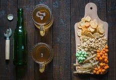 Πρόχειρα φαγητά σε μπύρα και δύο κούπες της ελαφριάς μπύρας, σε έναν ξύλινο πίνακα, σε έναν φραγμό Φυστίκια, φυστίκια σε ένα κοχύ Στοκ φωτογραφία με δικαίωμα ελεύθερης χρήσης