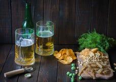 Πρόχειρα φαγητά στην μπύρα, σε ξύλινο πίνακα και δύο κούπες της μπύρας Τσιπ, φυστίκια, κομμάτια των ψαριών, κροτίδες, άνηθος, μπο Στοκ φωτογραφία με δικαίωμα ελεύθερης χρήσης