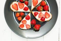 Πρόχειρα φαγητά των φρέσκων σάντουιτς με τις φράουλες σε έναν άσπρο πίνακα Υγιές πρόγευμα, τοπ άποψη στοκ εικόνες