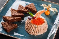 Πρόχειρο φαγητό από τις γαρίδες και κόκκινο χαβιάρι με το μαύρο ψωμί, που διακοσμείται με τα physalis και τα πράσινα στο πιάτο πέ στοκ φωτογραφία με δικαίωμα ελεύθερης χρήσης