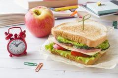 Πρόχειρο φαγητό για το σχολείο με το σάντουιτς, τη φρέσκια Apple και το χυμό από πορτοκάλι Ζωηρόχρωμες σχολικές προμήθειες Στοκ Φωτογραφίες